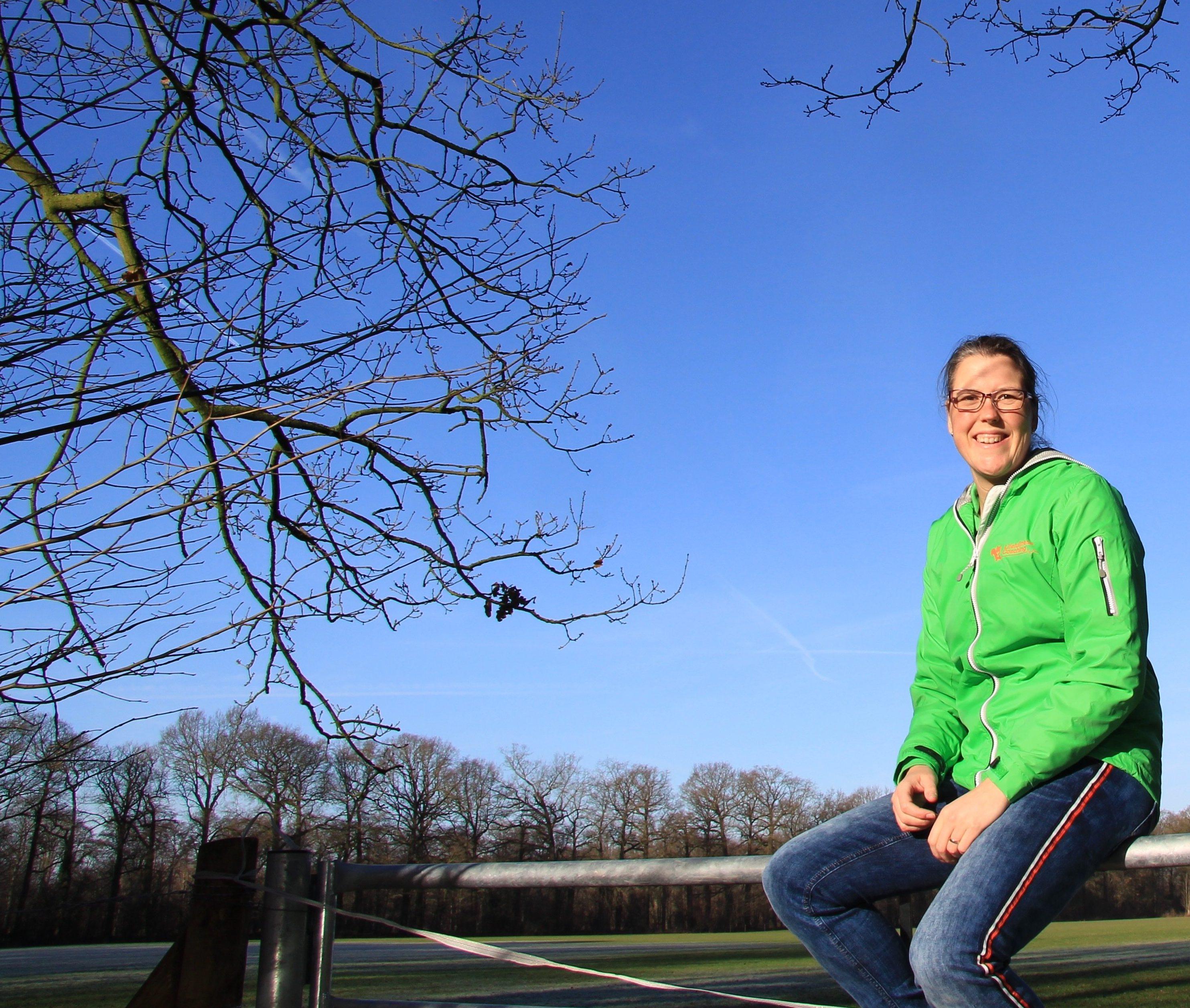 Sabine Jansen, eigenaar Lifefullness Coaching zittend in groene bedrijfskleding op Hek met zonnetje en fel blauwe lucht.