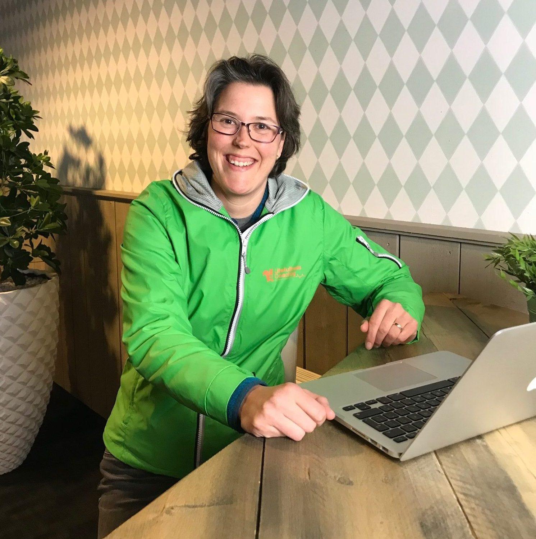 Foto van Sabine Jansen zittend achter een tafeltje netlaptop, wachtend naar de camera kijkend | Lifefullnesscoaching