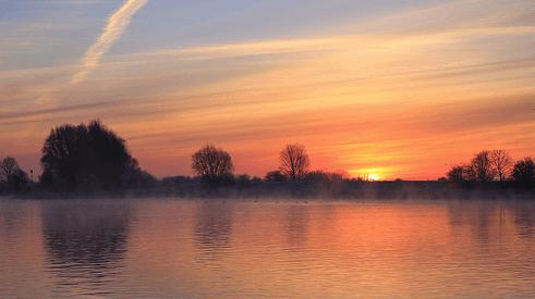 Morgenstond van opkomende zon langs de rivier